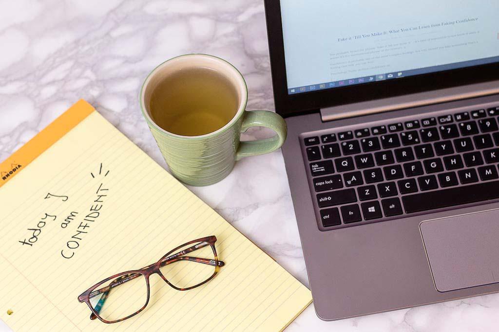 tea laptop notepad flatlay fake confidence